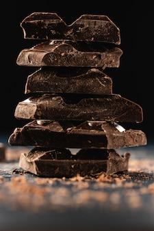 Стек из темного шоколада кусочки на темном. крупный план. копировать пространство