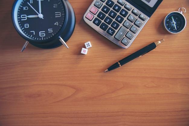 時計と木製のテーブルに書かれた税務計画の言葉