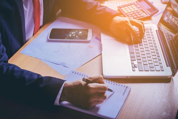 Закройте образ деловой человек в рубашке костюм пить кофе и проверить время на сотовый телефон. мужской фрилансер, отправляющий электронную почту после работы на портативном компьютере