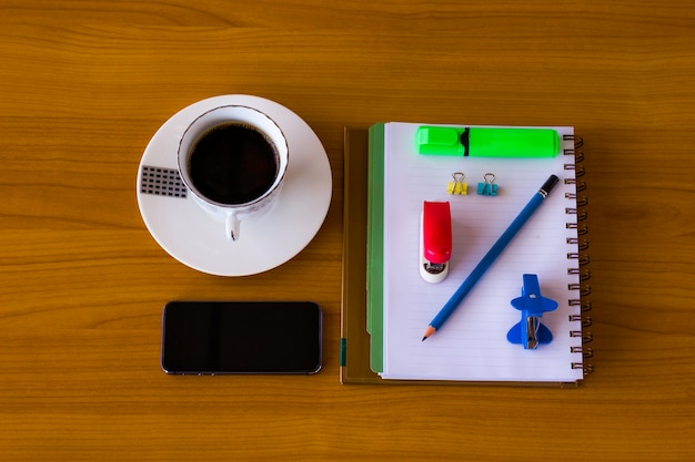 メモ帳と木製のテーブル上のコーヒーとマートフォン。