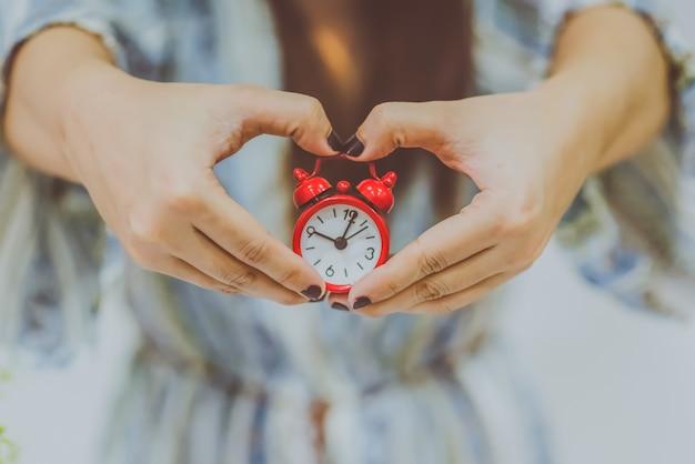 幸せな時間概念の良いオフィス計時の成功と喜びを示す手に大きな時計を持っている自信を持って優しい若い白人の女性