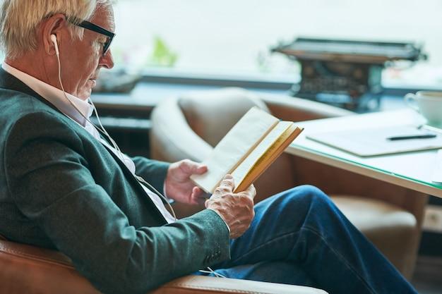 Старший мужчина читает книгу в кафе