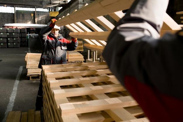 Рабочие завода переносят пеллеты на заводе