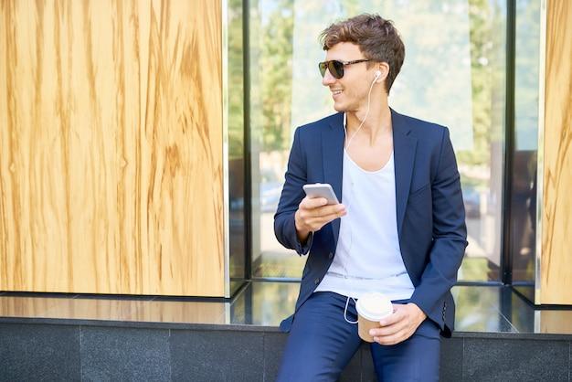 Модный молодой человек, расслабляющий с смартфон на открытом воздухе