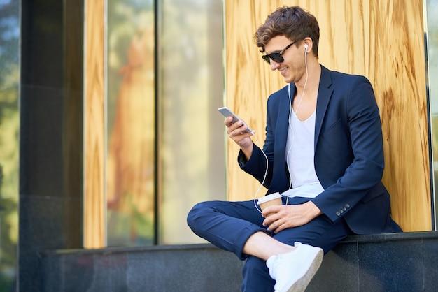 Стильный молодой человек с смартфоном на открытом воздухе