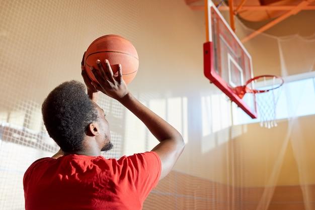 黒人男性がバスケットボールを投げる