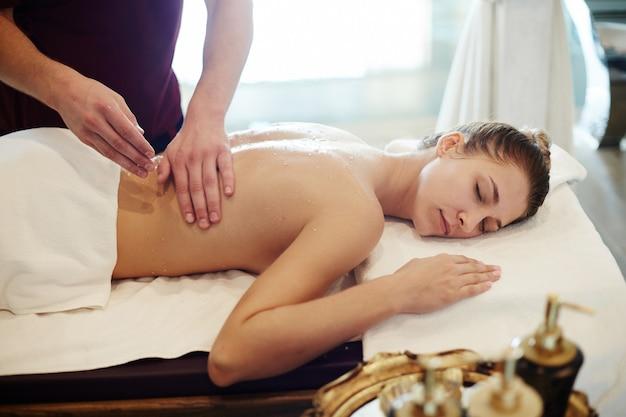 Молодая женщина наслаждается массажем в спа