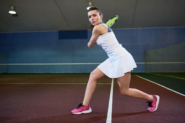 Энергичная молодая женщина играет в теннис