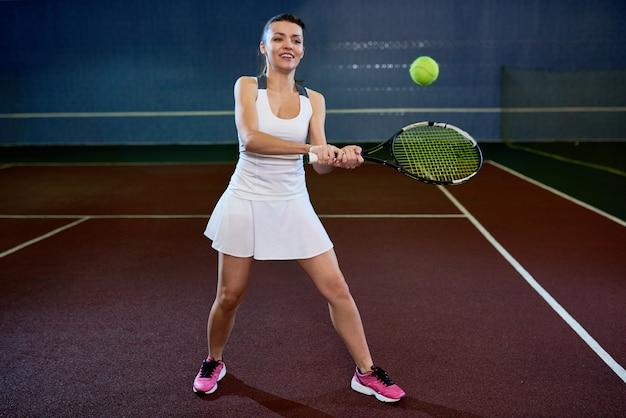 Молодая женщина играет в теннис