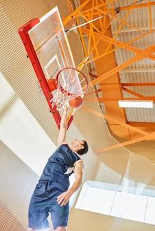 バスケットにボールを撮影する男