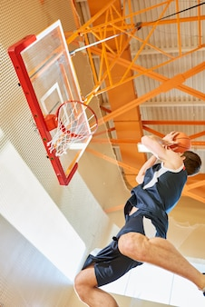 ジャンプしてボールをネットに投げるスポーツマン