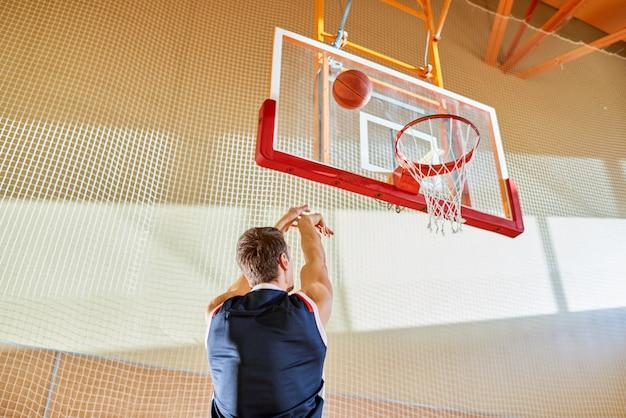 匿名のバスケットボール選手がボールを投げる