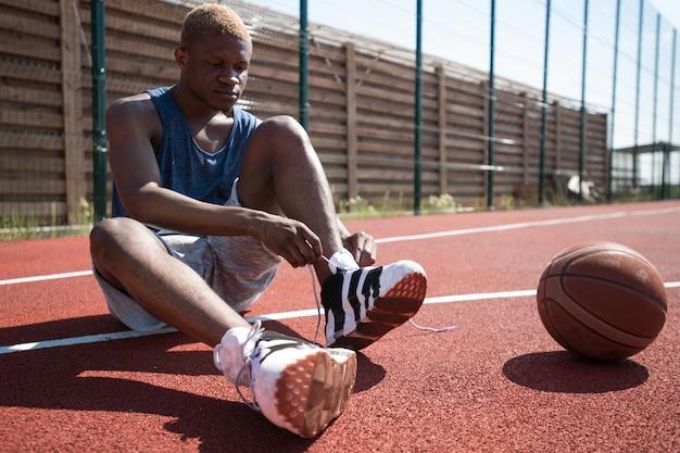 彼の靴を結ぶアフリカのバスケットボール選手