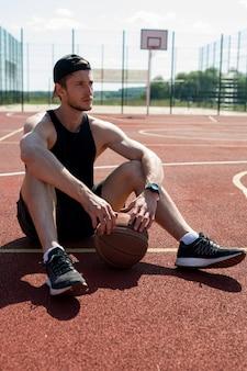 バスケットボールコートで休んで若い男