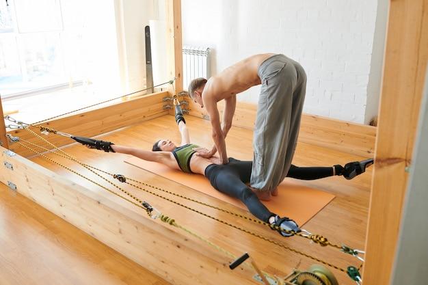 Терапевт йоги делает лечебный массаж женщине на трапеции йоги