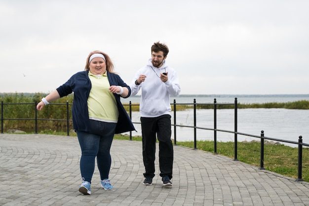 Тучная женщина, бегущая в парке