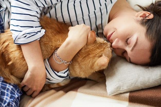 Молодая женщина обнимаются с кошкой