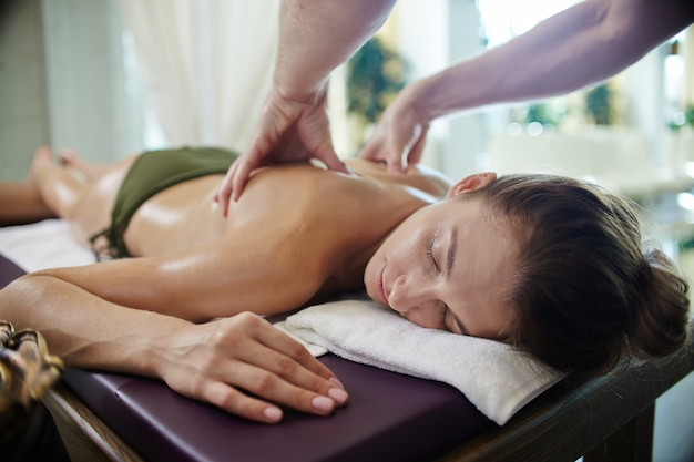 Молодая женщина, наслаждаясь массажем