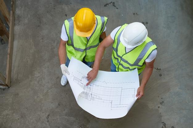 Вид сверху строителей, имеющих чертежи
