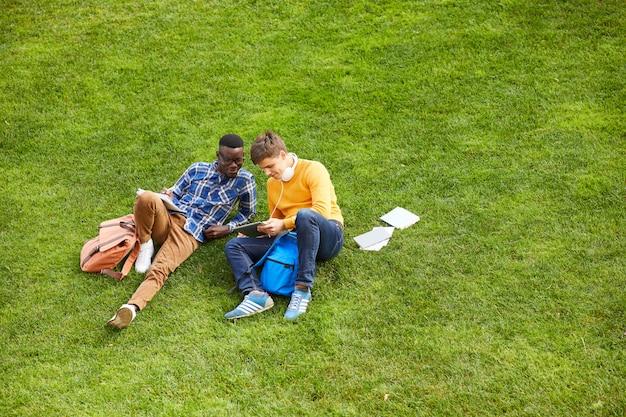 Студенты отдыхают на зеленой траве