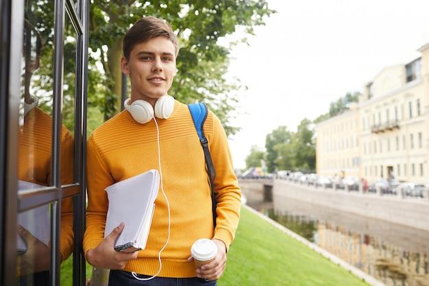 Молодой студент позирует на улице
