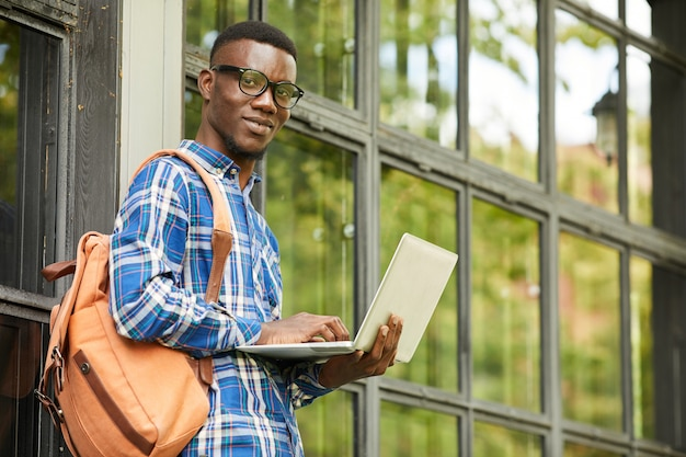 Африканский студент позирует с ноутбуком на открытом воздухе