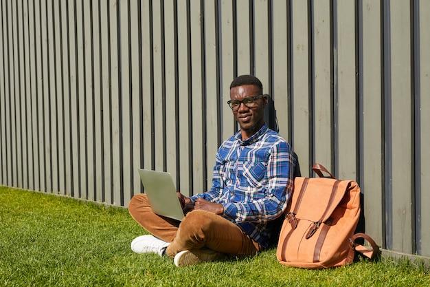Афро-американский студент, используя ноутбук в солнечном свете