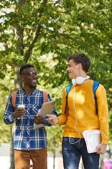 Студенты многоэтнического колледжа гуляют в кампусе