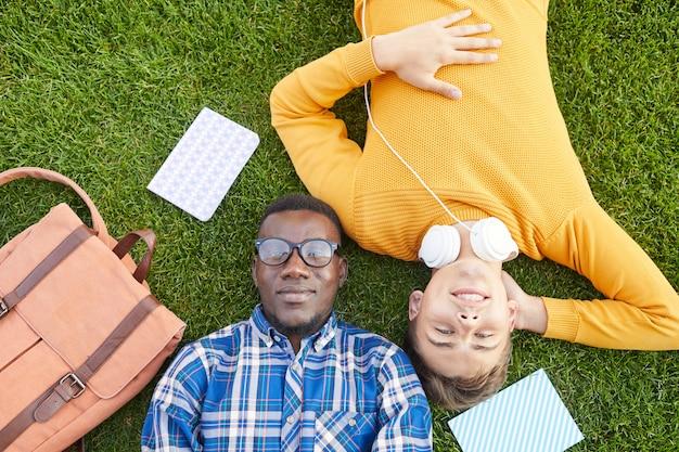 Двое студентов колледжа лежат на траве