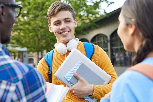 Группа студентов колледжа в чате на открытом воздухе