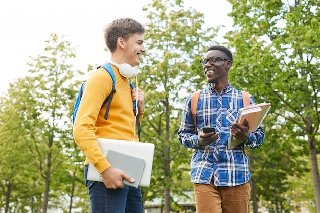 Двое молодых людей общаются в колледже