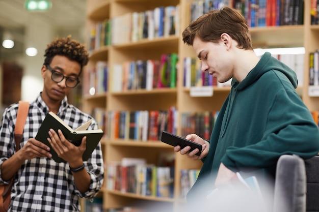 図書館で文学を選ぶ若い学生少年