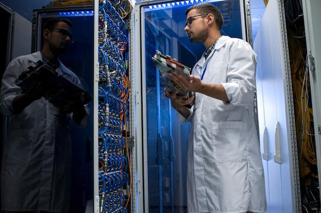Молодой техник работает с суперкомпьютером