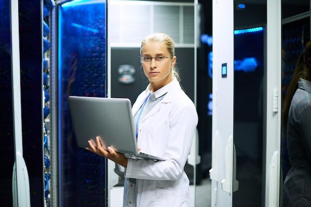 Женский ученый позирует с суперкомпьютером