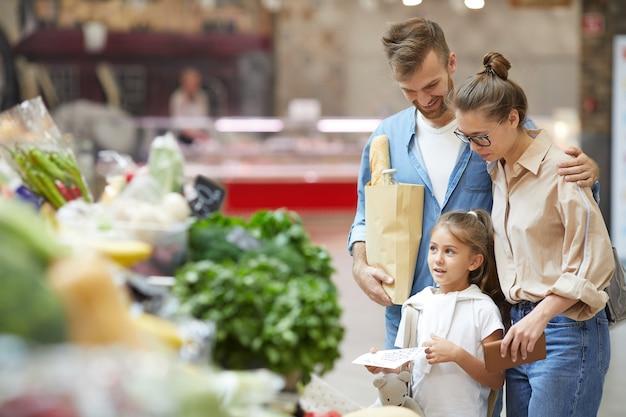若い家族の食料品を一緒に買い物
