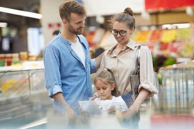 スーパーで幸せな家族の食料品の買い物