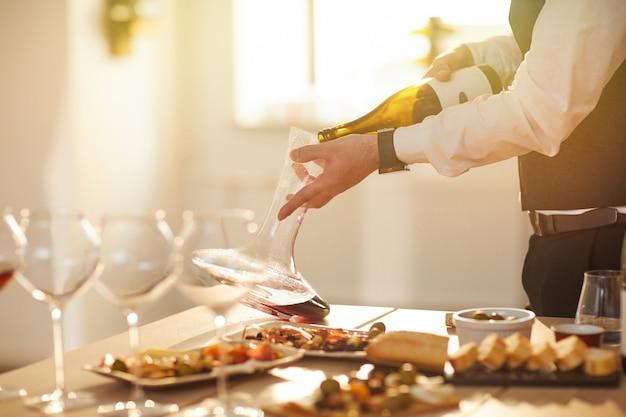 Сомелье наливая вино крупным планом
