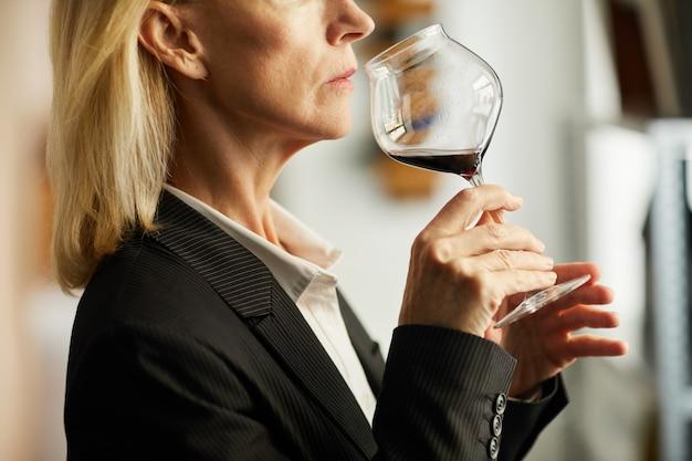 ワインのクローズアップの試飲の成熟した女性