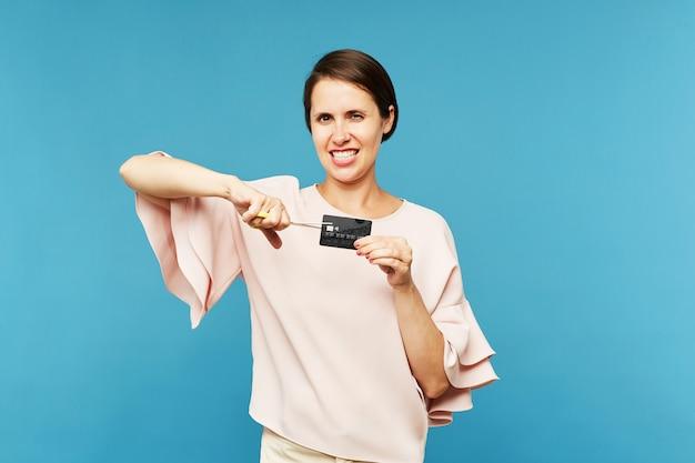 Молодой элегантный клиент резки ножом черная кредитная карта с ножницами