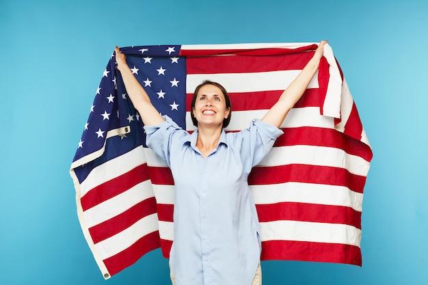 Счастливая молодая женщина с большим американским флагом