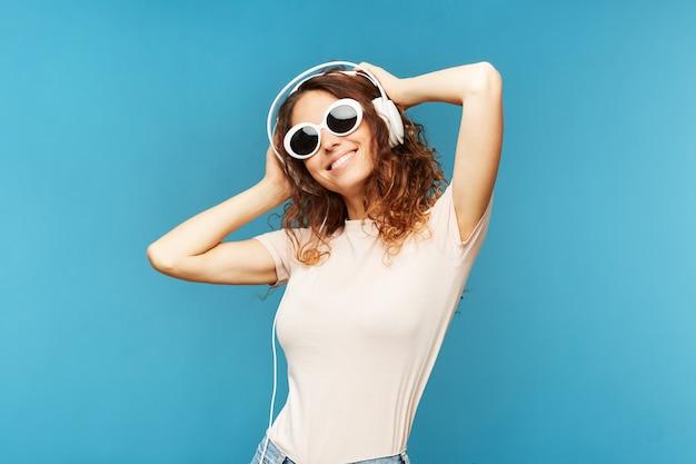 Молодая беззаботная брюнетка в джинсах и футболке слушает музыку