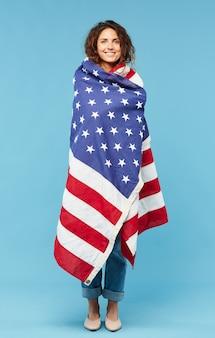 Счастливая молодая брюнетка женщина, завернутая в американский флаг