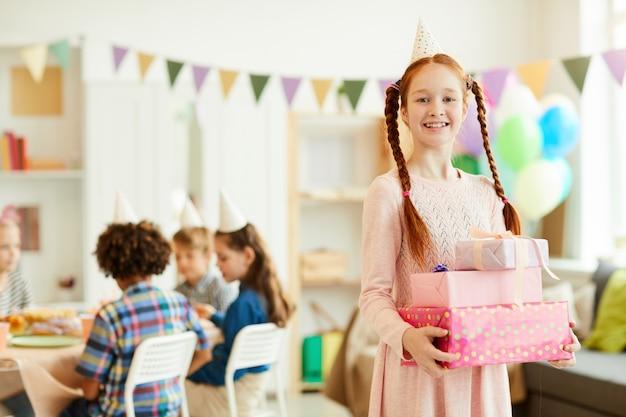Рыжая девушка держит подарки на день рождения