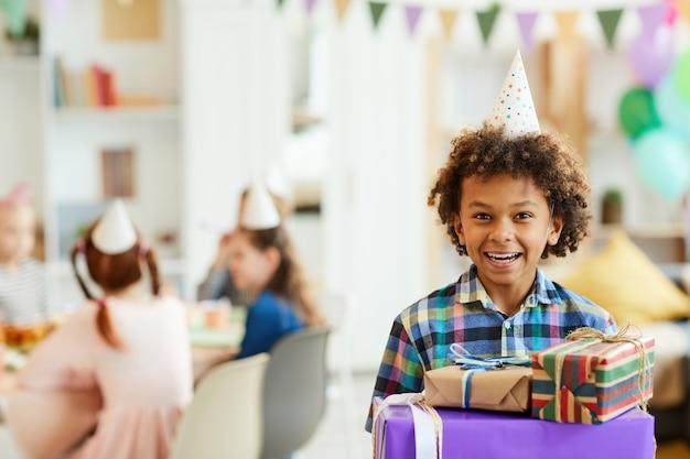 Счастливый мальчик держит подарки на день рождения
