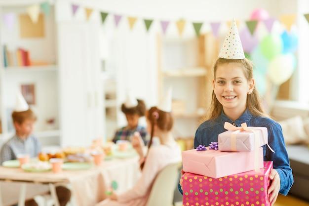 Улыбающаяся девушка держит подарки на день рождения
