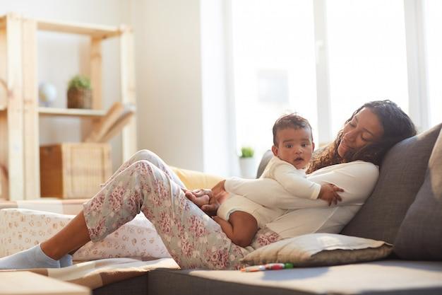 赤ちゃんと一緒にリラックスした慎重な母