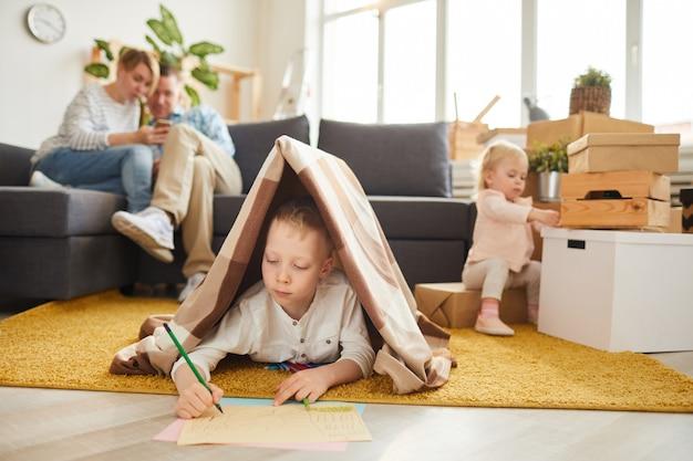 彼の家族のために新しい家を描く少年