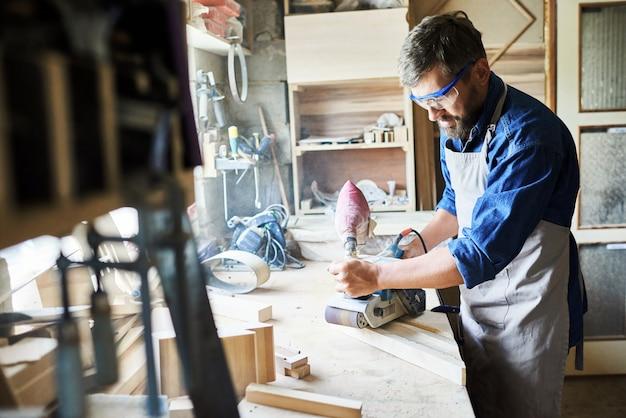 Карпентер шлифование дерева в мастерской