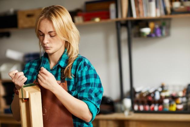 革のバッグを作る女性