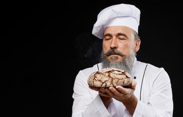 ひげを生やしたパン屋の新鮮なパンを保持